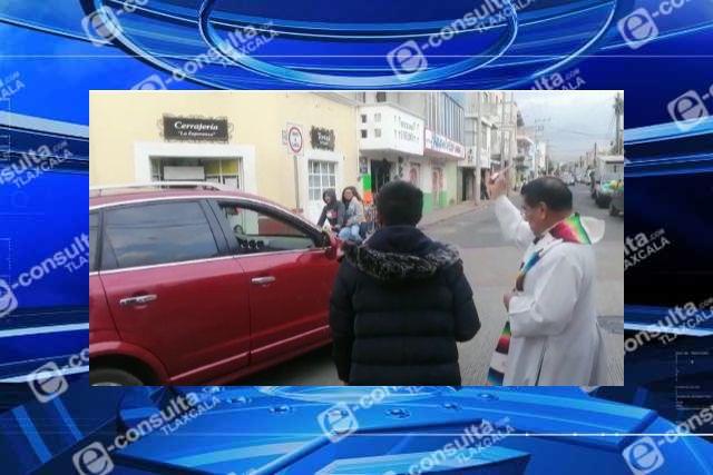 Ante la ineptitud del Don Cheto, sacerdote rocía agua bendita en la vía publica