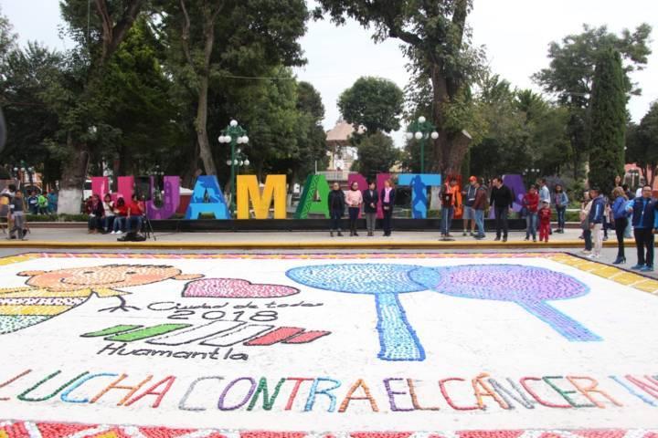 Elaboran tapete monumental con tapas de botellas en beneficio de niños con cáncer